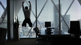 Image of man jumping in office before large windows with city views